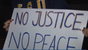 "Person holds up ""no justice, no peace"" sign"