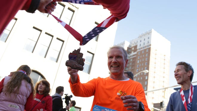 Richard Lehto, 56, of Auburn Hills reaches for his medal after finishing the full marathon during the 37th Annual Detroit Free Press/Talmer Bank Marathon in Detroit on Oct. 19.