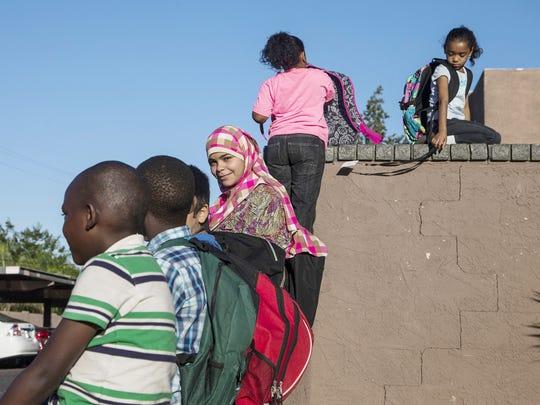 Hoda Hamsah, 12, center, waits for the school bus.