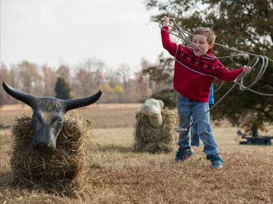 Brantley Jackson, 5, twirls the rope around him as he practices getting it around the roping dummy's head while at Blue Moon Stables for Christmas on the Farm in Corydon, Ky., on Saturday afternoon.