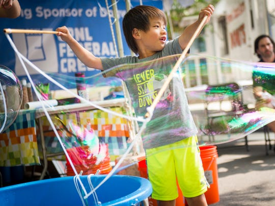 Russel Giam watches as he makes a giant bubble in the