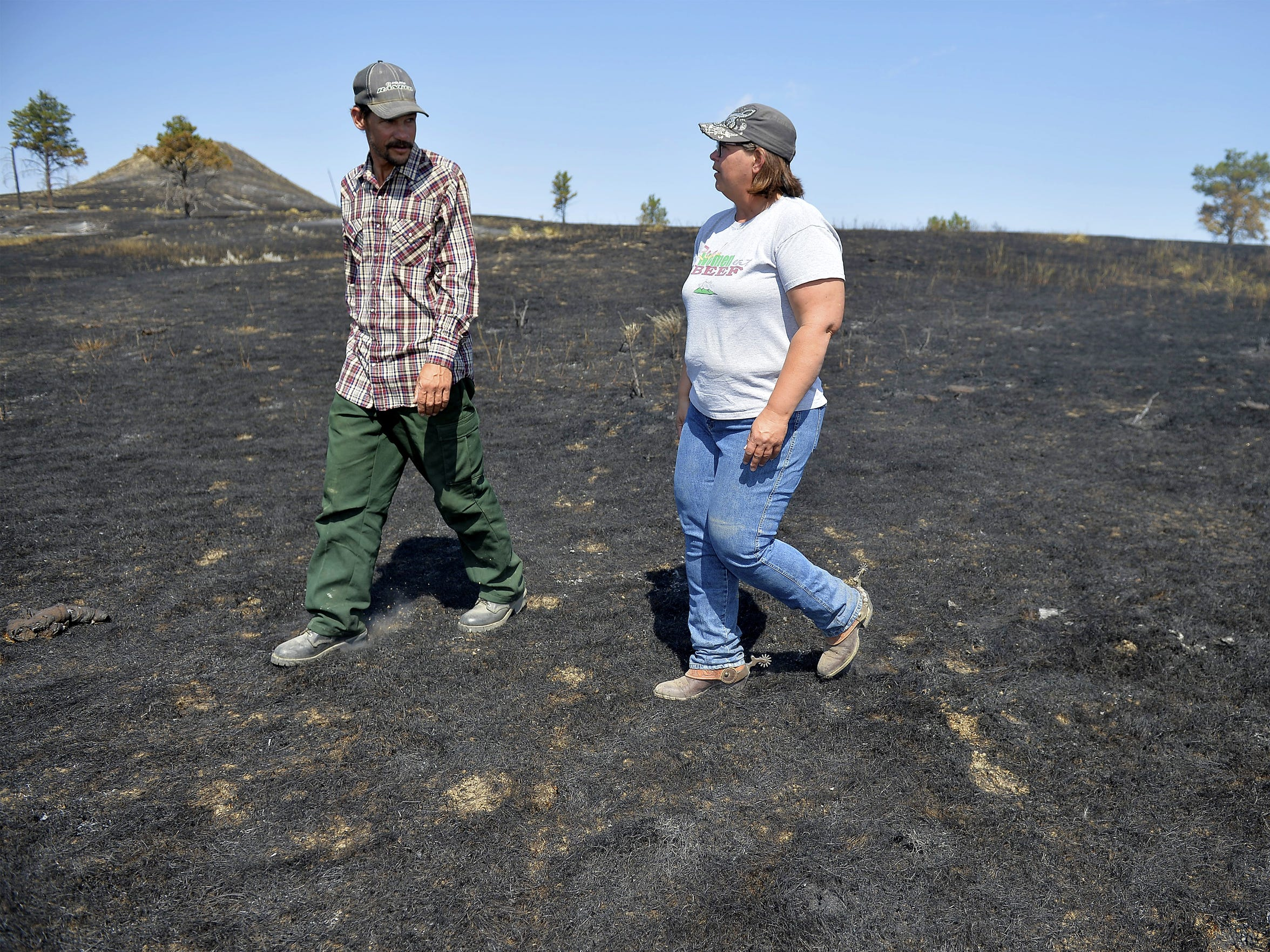 Matt and Jeana Bliss walk across their fire scarred property on Wednesday morning as they begin the recovery effort in the aftermath of the Lodgepole Complex fire.