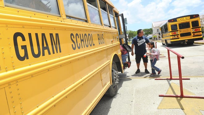 In this file photo, bus driver Cris Cali assists students as they board a bus to go home at Tamuning Elementary School.