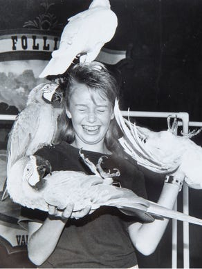 """1990: Laurie Borst, 12, gets a handful of macaws and cockatoos during the """"Have Birds: Will Travel"""" show at Great Adventure."""