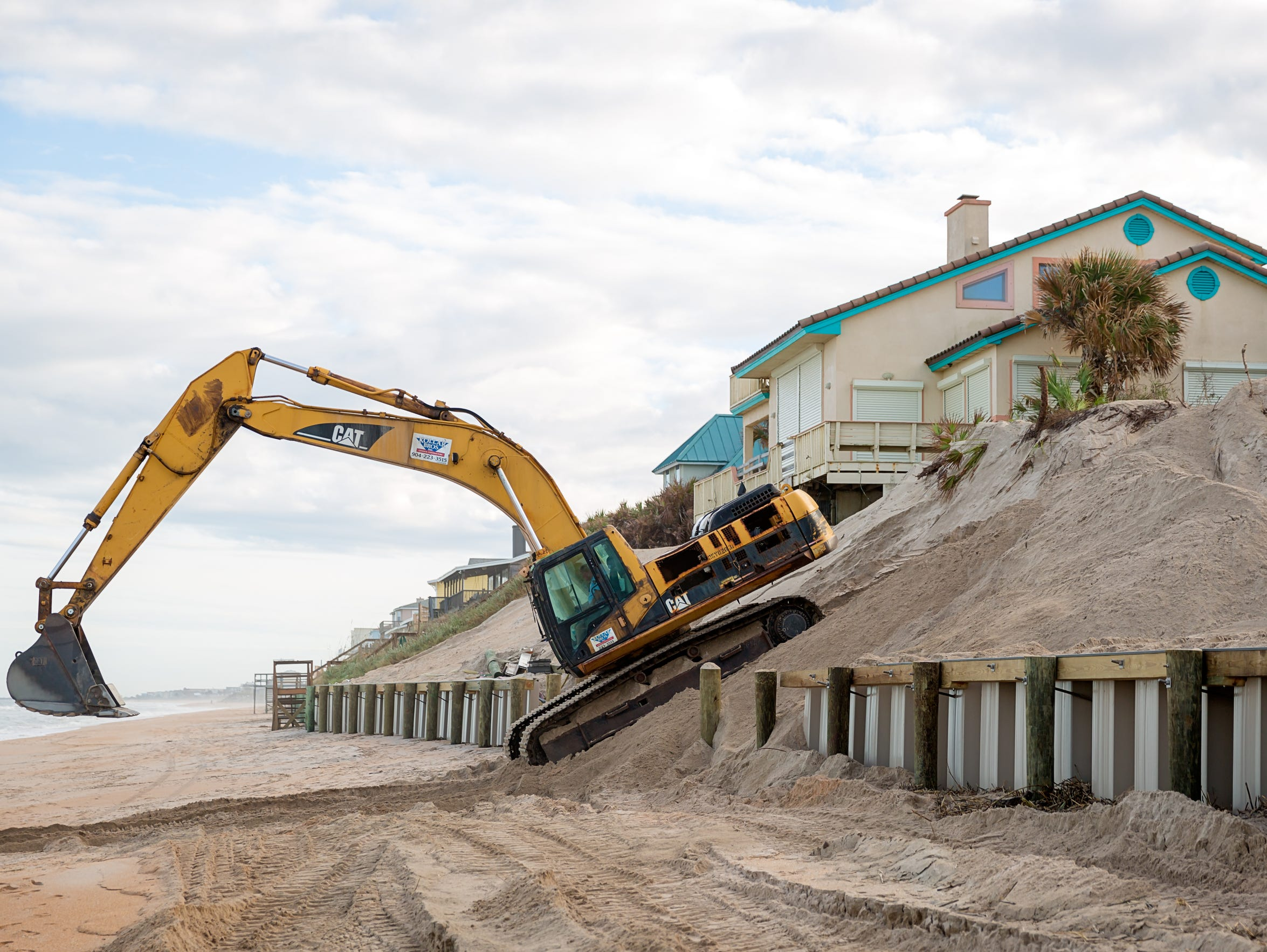 An excavator is used to build a sea wall in Vilano