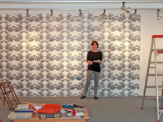 Anne Dushanko Dobek installing And Again, the vinyl