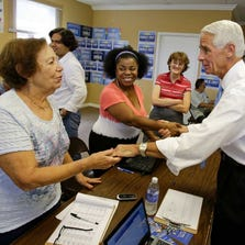 Former Florida Gov. Charlie Crist, right, thanks campaign volunteers for their support during a visit to a calling bank Monday, Aug. 25, 2014, in Orlando.