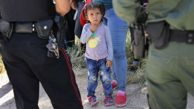 A Mission Police Dept. officer (L), and a U.S. Border Patrol agent watch over a group of Central American asylum seekers before taking them into custody on June 12, 2018 near McAllen, Texas.