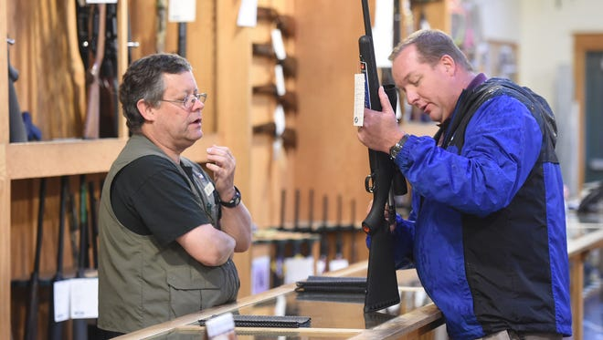 Sales person, Jim Miles, left, shows a hunting rifle ot customer, Steve Young, right, of Fort Collins, in the hunting department at Jax Outdoor Gear Thursday Oct. 9, 2014.