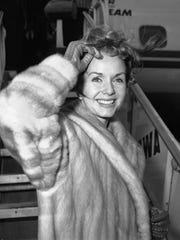 "FILE- In this March 6, 1959, file photo actress Debbie Reynolds boards an airliner in New York en route to Spain where she will film a new picture. Reynolds, star of the 1952 classic ""Singin' in the Rain"" and mother of Carrie Fisher, died Wednesday, Dec. 28, 2016, according to her son Todd Fisher. She was 84."