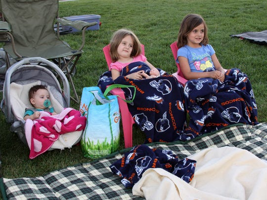 Sophia, Lily and Chloe Marlow get comfortable Friday while watching the movie, 'Frozen,' at Boardwalk Park. Movies in the Park on Friday nights are free to the public.