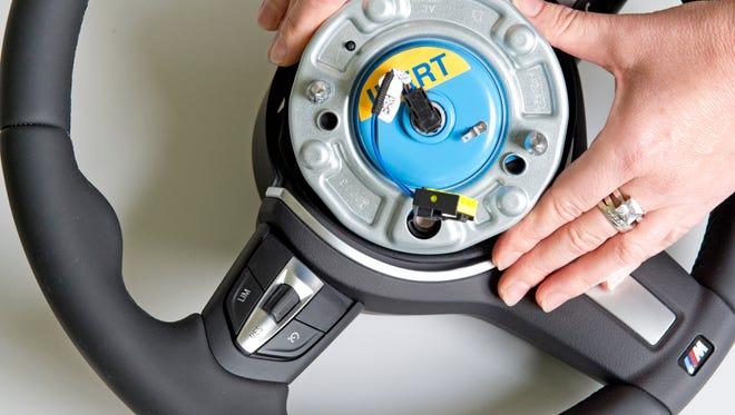 A worker demonstrates a Takata steering wheel airbag initiator.