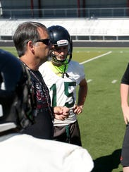 Head Coach Jeff Flood talks to his players during football