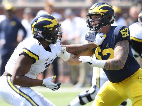 Mason Cole, right, played left tackle and center at Michigan.