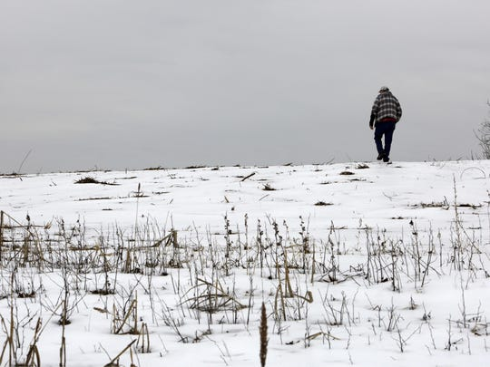 In this Saturday, Feb. 23, 2019 photo, Mike Carpenter, uncle of Greg Longenecker, walks the field where Longenecker was killed by a bulldozer in 2018, in Bernville, Pa. A federal lawsuit file Monday, March 18 accuses Pennsylvania State Police of gross recklessness for using a bulldozer to chase and inadvertently run over and kill Longenecker, who had fled after being caught growing marijuana on public land. (AP Photo/Jacqueline Larma)