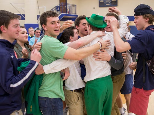 Students hug a leprechaun hopeful after his tryout