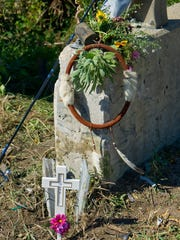A cross and flowers sit at the crash site where two