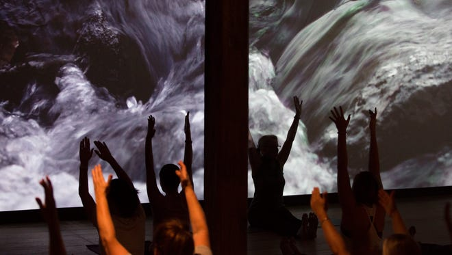 """Yoga practitioners take part in a class set in the exhibition """"Dylan Gauthier: highwatermarks,"""" at the Brandywine River Museum of Art. The immersive exhibit pairs wall-size projections of Brandywine River valley video scenes with audio recorded at those locations."""