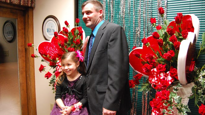 Bill Westrick has his photo taken with his daughter, Abigail, 6, during the Daddy-Daughter Valentine's Dance in St. Clair.