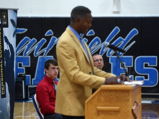 Ryder Meyer (seated at left)  and his father Les (right) look on as NFL Hall of Fame cornerback Mike Haynes speaks in the Fairfield High School gym on Wednesday. Haynes was on hand to officially name Ryder a U.S. Army/Pro Football Hall of Fame Award for Excellence finalist.
