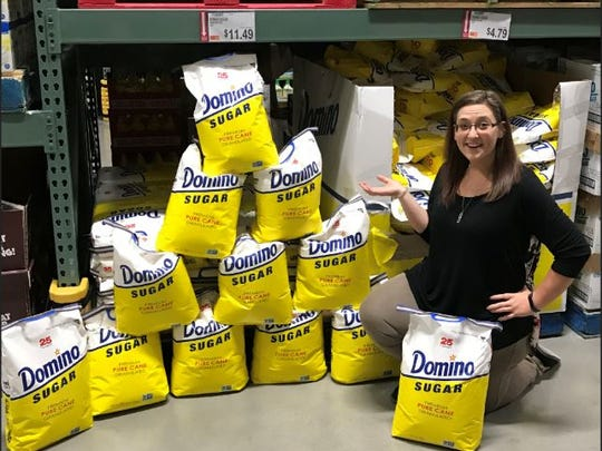 Brittany May poses with 12 25-pound bags - 300 pounds
