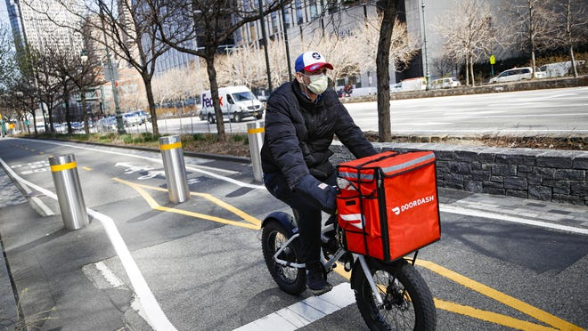 A delivery worker traverses a bike path along the West Side Highway in New York in mid-March.