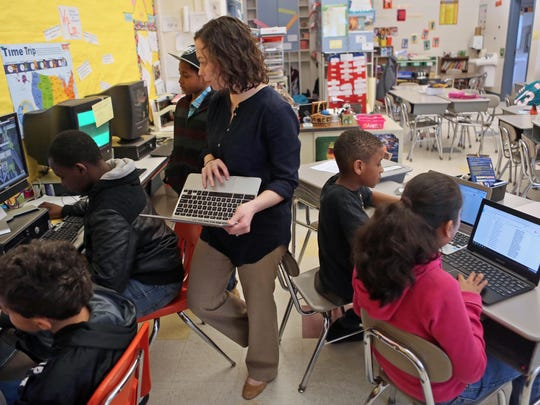 Fifth-grade teacher Katy Corey at Carrie Downie Elementary School oversees her students as they work independently and in small groups assembling a school newspaper in the Schoology program.