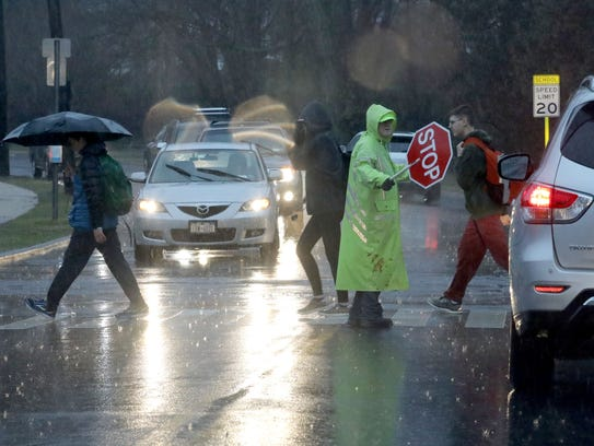 A school crossing guard assists students on Milton