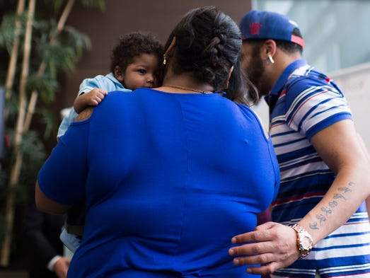 Camden resident Jernica Quinones, center, carries her