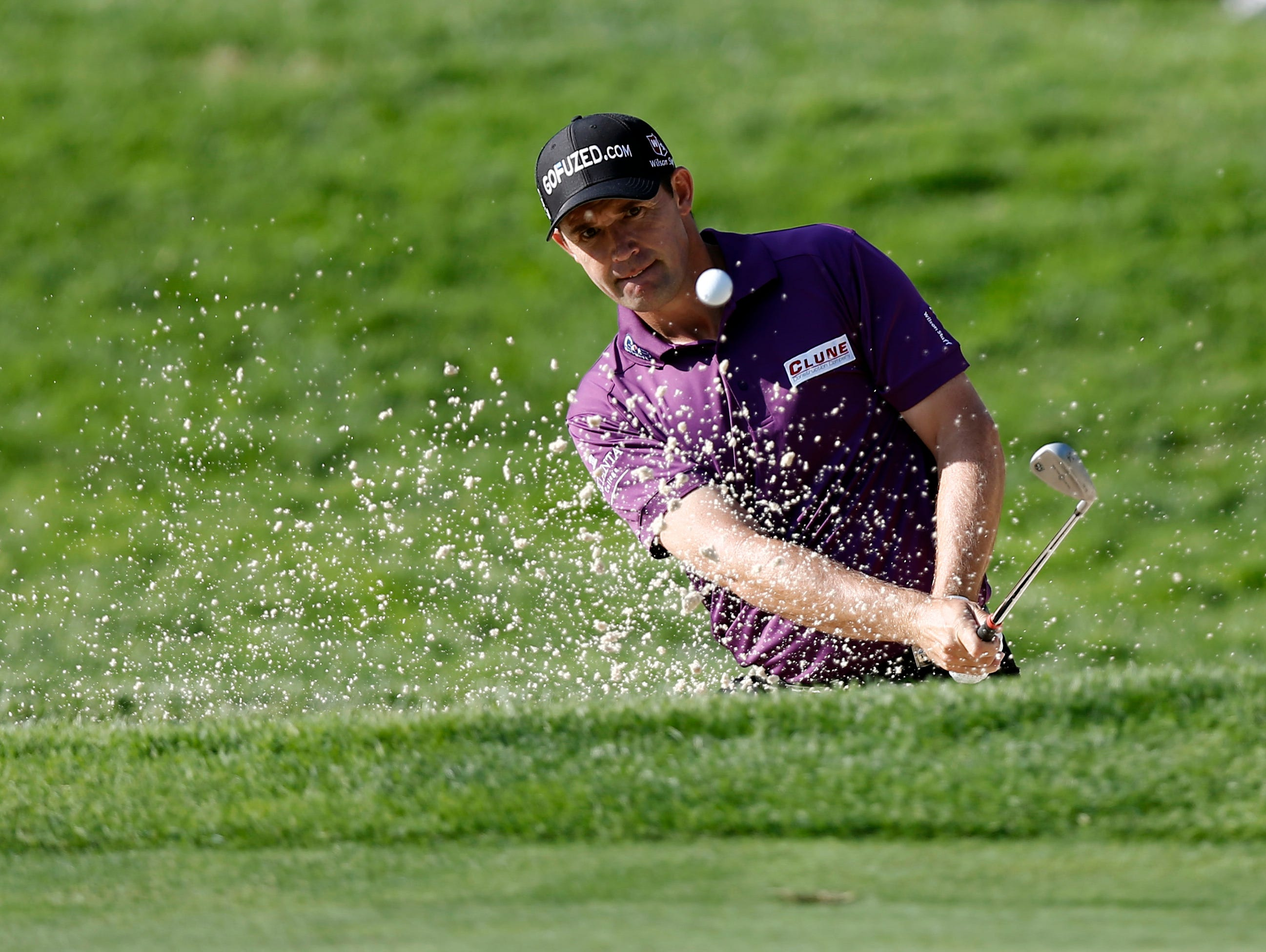 Padraig Harrington plays out of a green side bunker on the 11th hole during the first round of the 95th PGA Championship at Oak Hill Country Club.