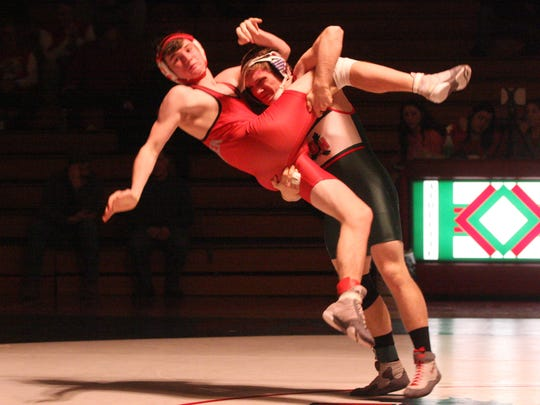 Oak Harbor's Garrett Mapes throws Bellevue's Braxton Berry to the mat.
