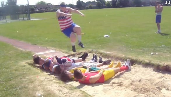 A man attempts to long jump over friends. It doesn't go well for the guy in the yellow shorts.