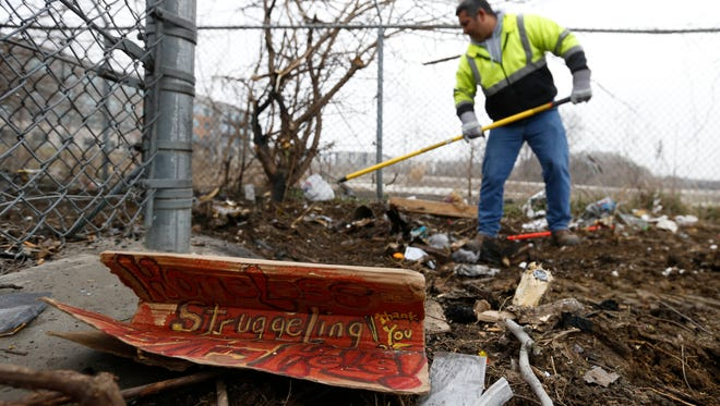 A sign asking for donations sits on the ground as Jose Marrero with the City of Des Moines' property rakes out some of the remaining debris Wednesday, March 23, 2016, as crews clear out a homeless camp site near the intersection of Southwest 11th Street and Martin Luther King Parkway in Des Moines.