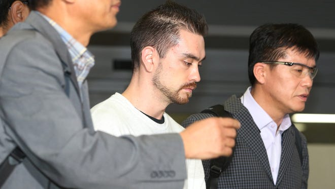 In this Sept. 23, 2015, file photo, Arthur Patterson, center, an American charged with murdering a Seoul university student in 1997, is escorted by South Korean police officers upon his arrival at Incheon International airport in Incheon, South Korea.