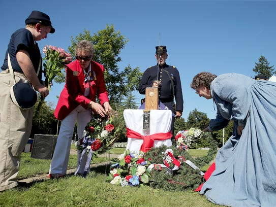 Mourners, dressed in period costumes, place memorial