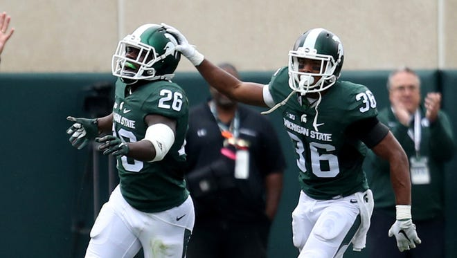 Michigan State's RJ Williamson, left, celebrates with Arjen Colquhoun, right, after he intercepted Air Force's Karson Roberts during second-half action Sept. 19, 2015, at Spartan Stadium in East Lansing.