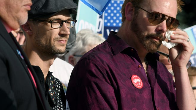 Charlie Craig, right, and his partner, Dave Mullins, participate in a rally after the Supreme Court ruled in favor of a baker who refused to make a cake for their wedding on June 4, 2018.