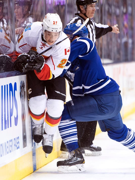 Toronto Maple Leafs defenceman Cody Franson, right, hits Calgary Flames forward Mason Raymond (21) during the first period of an NHL hockey game in Toronto on Tuesday, Dec. 9, 2014. (AP Photo/The Canadian Press, Nathan Denette)