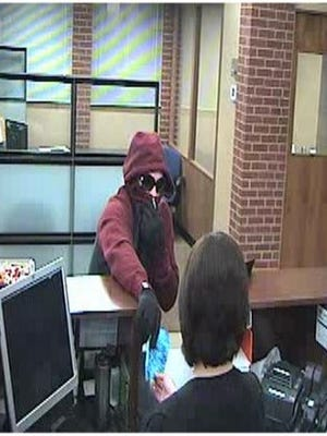 In this image from video surveillance at Chase Bank in Allouez, a man presents a note demanding money to an employee inside the bank at closing time Friday night, Nov. 4, 2016. The robber fled on foot with an undisclosed amount of money.