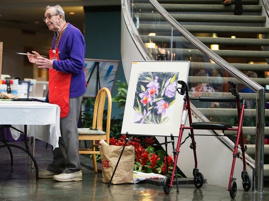 Plato Pavis, 96, paints during his exhibit Thursday at HealthPark Medical Center in south Fort Myers. Pavis has volunteered at HealthPark since 2000 and is painting tiles for the healing ceilings project of Lee Memorial's arts in healthcare program.