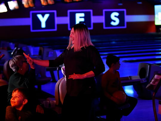 Kimberly Florit from Lake Hopatcong, gives a high-five after bowling a strike at the rebranded Bowlero lanes in Fair Lawn.