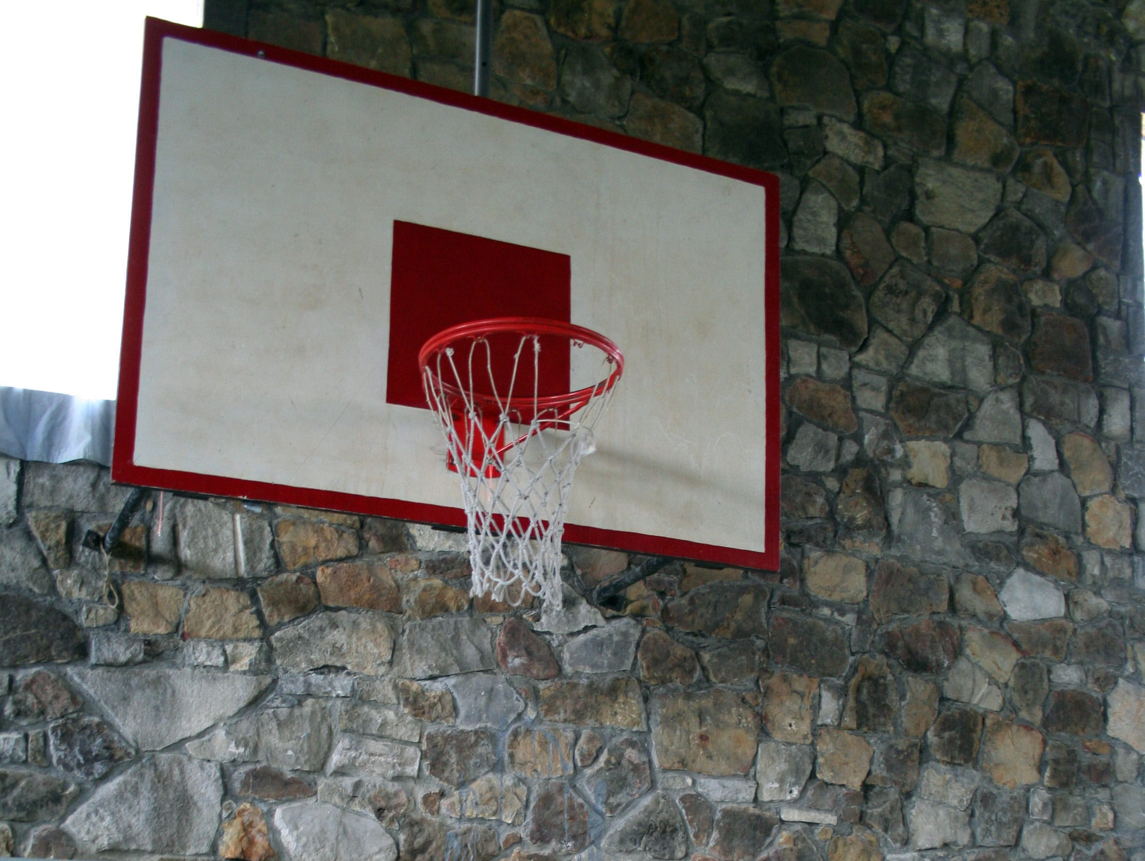 FILE – Little more than a foot separates the basket from the stone wall in the Springville gym.