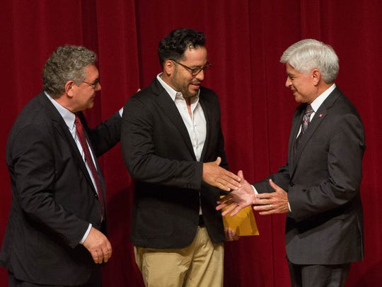 John Floros, left, president of New Mexico State University along with Dan Arvizu, right, chancellor of NMSU congratulate Ernesto Morales, center,  a professor in the department of Public Health Sciences was presented with the Patricia Christmore Faculty Teaching award, Tuesday August 14, 2018 at the 2018 Fall Convocation in Atkinson Recital Hall.