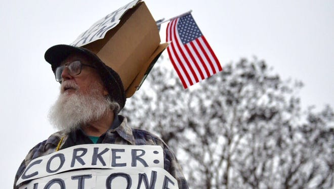 Wearing a cardboard top hat reading 'GOP Tax Scam,' Richard Zook, of Jackson, protests the GOP tax bill Tuesday, Dec. 19, 2017, at the intersection of Lafayette Street and Highland Avenue in Jackson.
