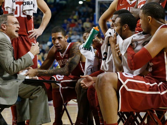 Oklahoma head coach Lon Kruger, left, talks with his players during a timeout in the first half of an NCAA college basketball game against Tulsa in Tulsa, Okla., Saturday, Dec. 13, 2014. Oklahoma won 87-68. (AP Photo/Sue Ogrocki)