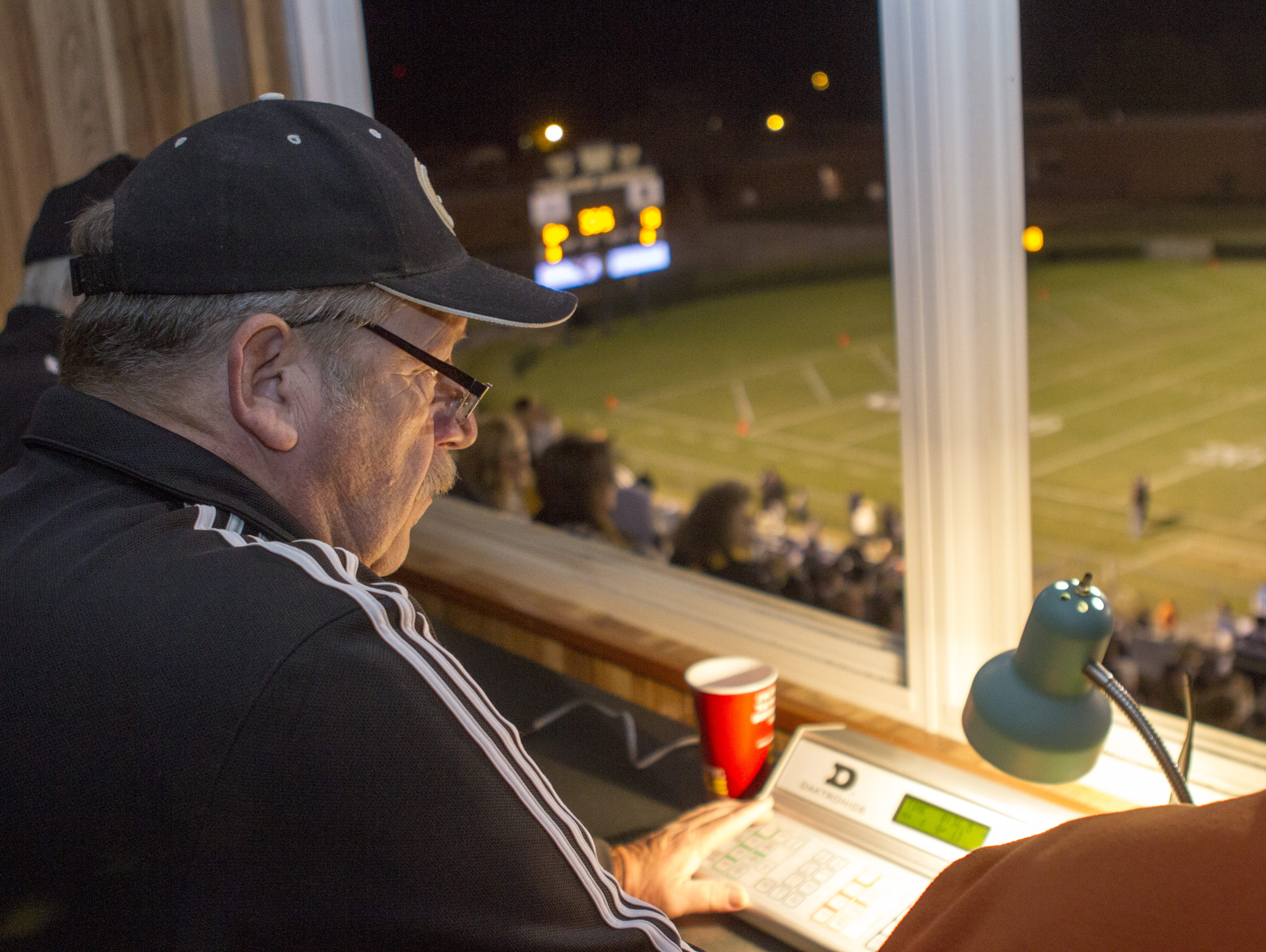 Phil Crain watches to see if Greer High School gets the extra point, after adding the Yellowjackets' first score to the board. Crain runs the scoreboard at the school, and beside him to the left Gary Vaughn, who operates the 25-second clock. On his right is Jeff McCoy, an official with the South Carolina High School League overseeing the scoreboard dring the playoff game with Travelers Rest.