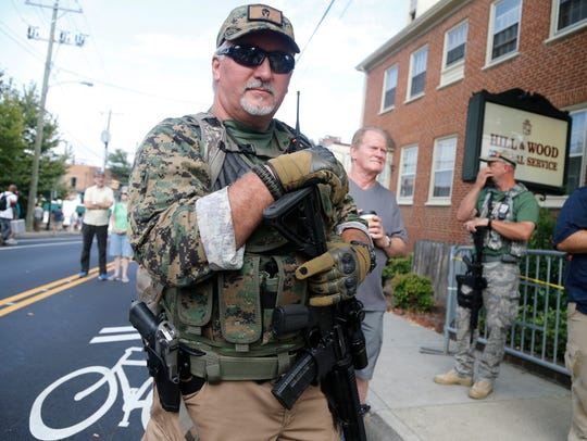 An armed militia member stands guard at the white nationalist rally in Charlottesville on Aug. 12.