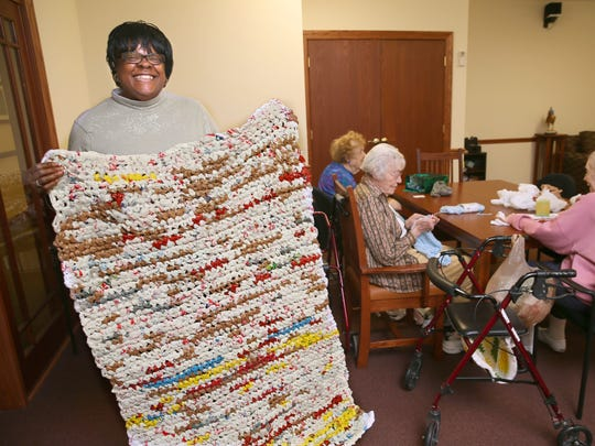 Volunteer Darlene Liston displays a finished Mercy Mat.