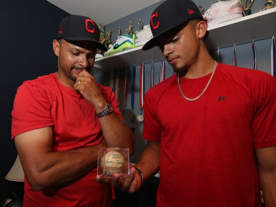 Lenny Torres with his son, Lenny Torres, Jr. at their home in Beacon on June 13, 2018.  Lenny Jr. recently signed with the Cleveland Indians. They are looking at Jr's souvenir baseball from when he hit his first home run.