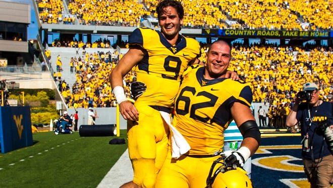 Clint Trickett and offensive linesman Curtis Feigt celebrate after the win.